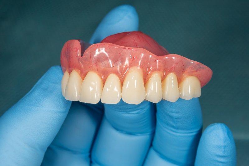 an up-close image of a gloved hand holding an upper denture